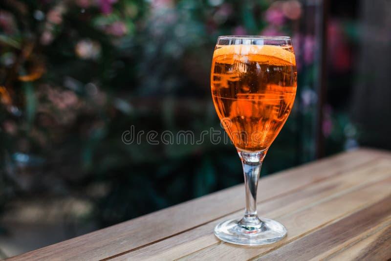Aperol spritz o cocktail no vidro na tabela de madeira no fundo escuro no café fotos de stock