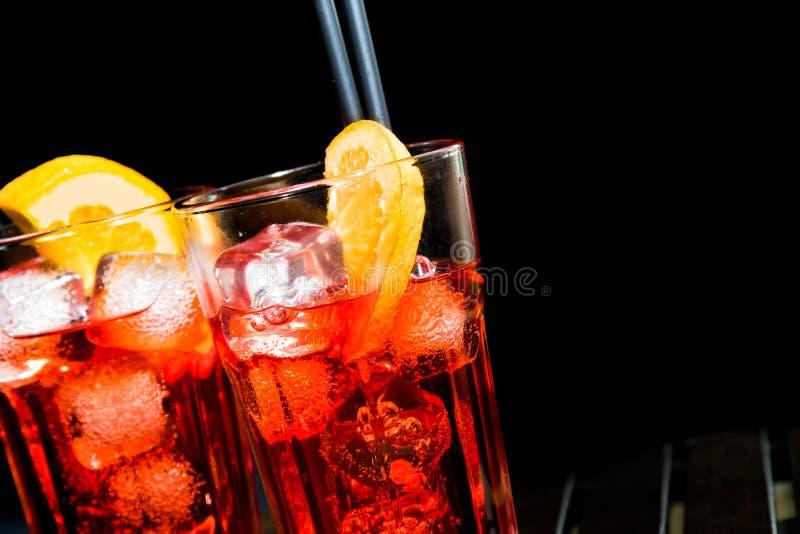 Aperolcocktail van het Spritzaperitief met oranje plakken en ijsblokjes op zwarte royalty-vrije stock fotografie