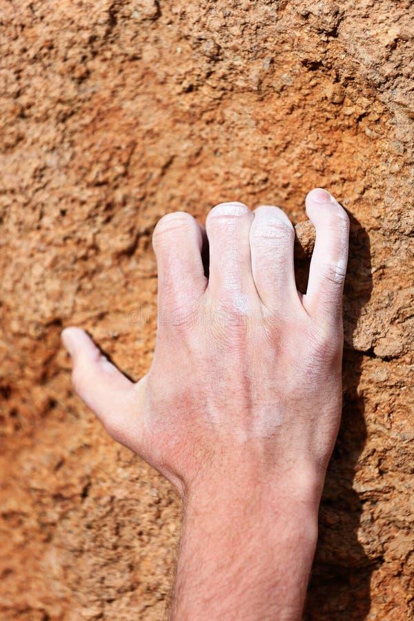 Aperto de escalada da mão na rocha imagens de stock royalty free