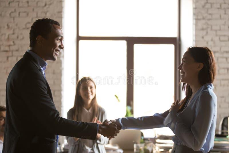 Aperto de mão afro-americano do empregador que felicita o trabalhador fêmea entusiasmado fotografia de stock