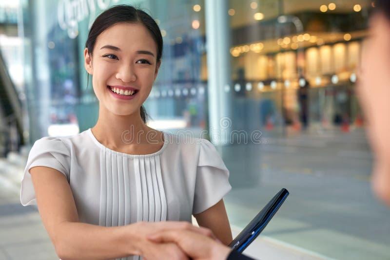 Aperto de mão asiático da mulher de negócio fotos de stock