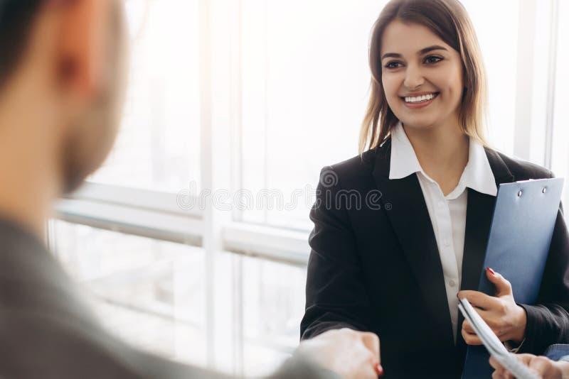 Aperto de mão atrativo de sorriso da mulher de negócios com o homem de negócios após a conversa agradável, bons relacionamentos F foto de stock royalty free