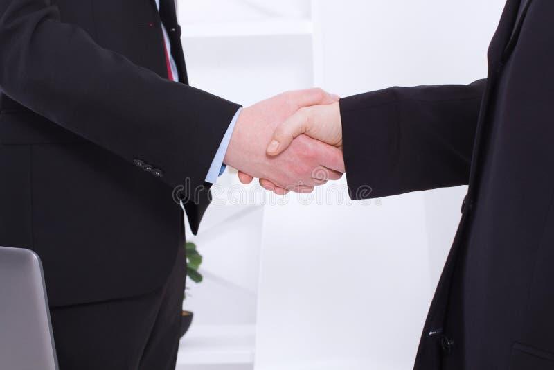 Aperto de mão bem sucedido à moda dos homens de negócios após o negócio rentável no fundo do escritório Imagem do aperto de mão d fotografia de stock royalty free