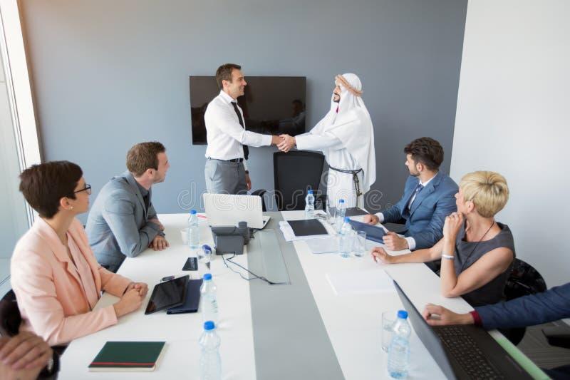 Aperto de mão bem sucedido do homem de negócios com sócio árabe imagem de stock