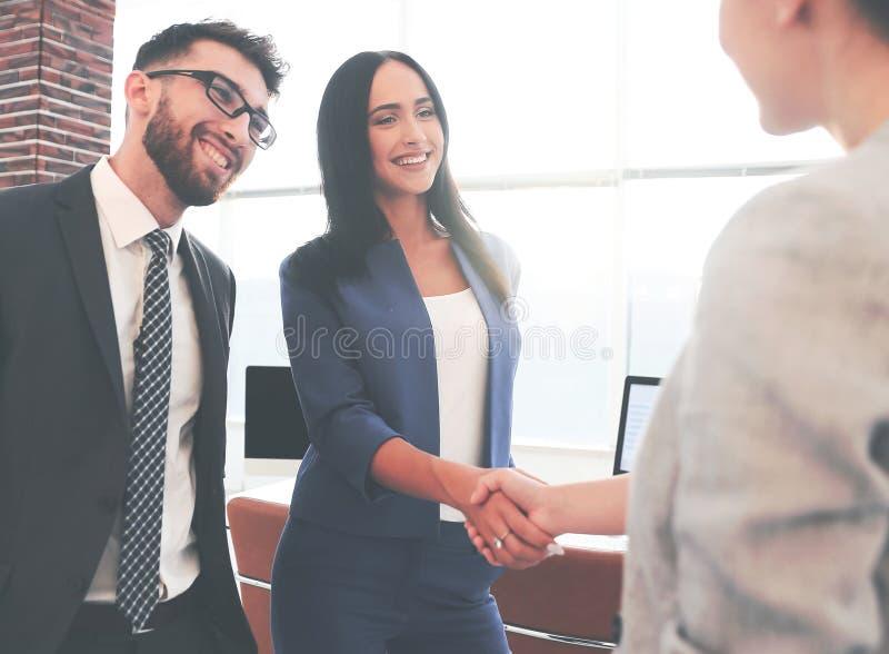 Aperto de mão bonito de duas mulheres de negócios no escritório imagem de stock