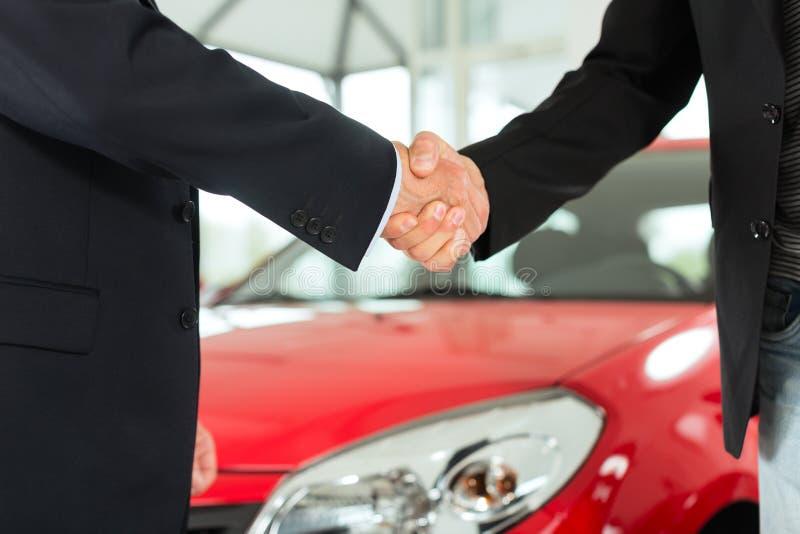 Aperto de mão de dois homens nos ternos com um carro vermelho fotografia de stock royalty free