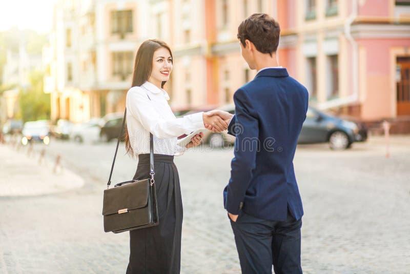Aperto de mão de sorriso do homem de negócios e das mulheres de negócios para uma reunião de negócios exterior foto de stock royalty free