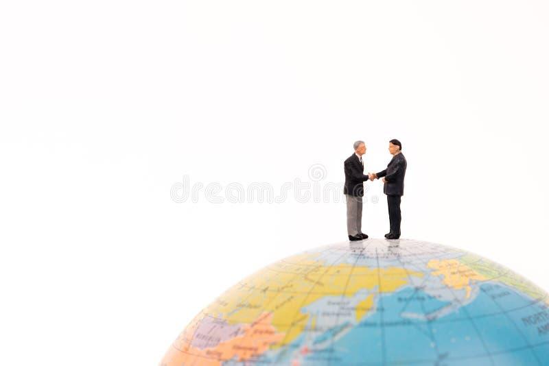 Aperto de mão diminuto dos povos do negócio no globo imagens de stock