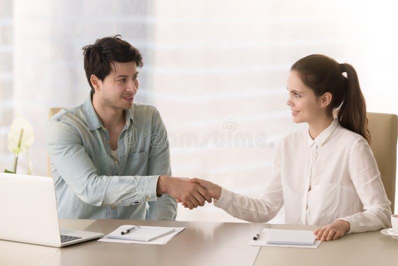 Aperto de mão do cumprimento da mulher de negócios e do homem de negócios que sentam-se em b fotos de stock