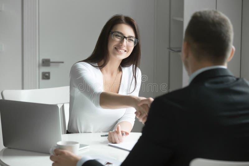 Aperto de mão do homem de negócios e da mulher de negócios sobre a mesa de escritório fotografia de stock