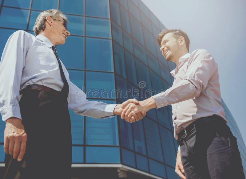 Aperto de mão de dois homens de negócios bonitos contra foto de stock royalty free