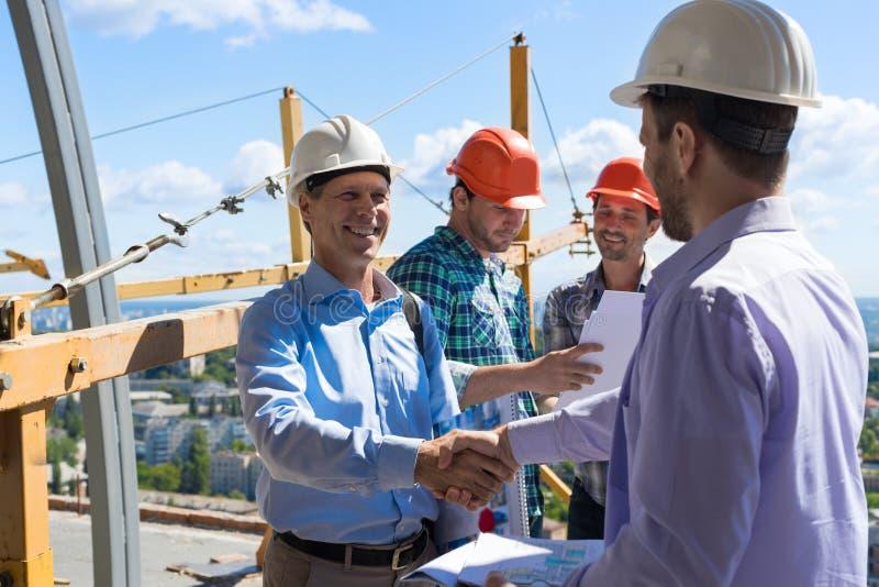 Aperto de mão dos construtores, dois sócios de sorriso felizes que agitam a mão após ter encontrado o contramestre Team On Site fotografia de stock royalty free