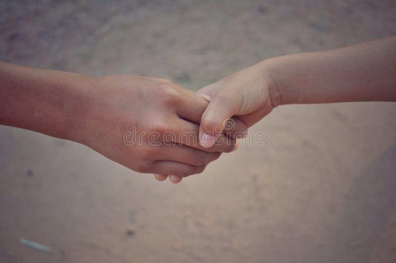 Aperto de mão entre duas mãos imagem de stock