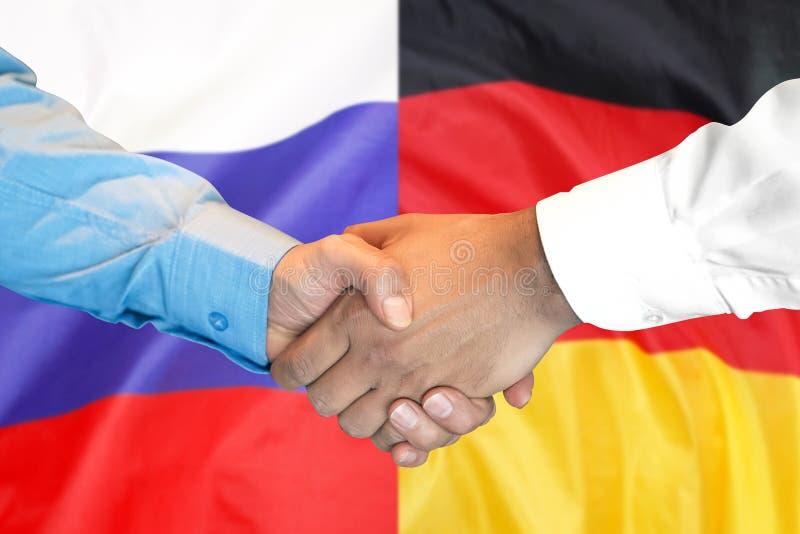 Aperto de mão fundo na bandeira de Alemanha e de Rússia foto de stock