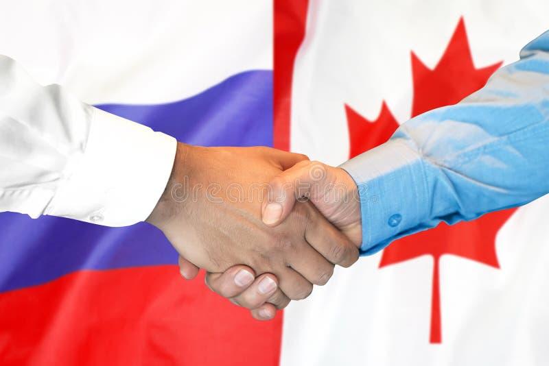 Aperto de mão fundo na bandeira de Canadá e de Rússia imagem de stock royalty free