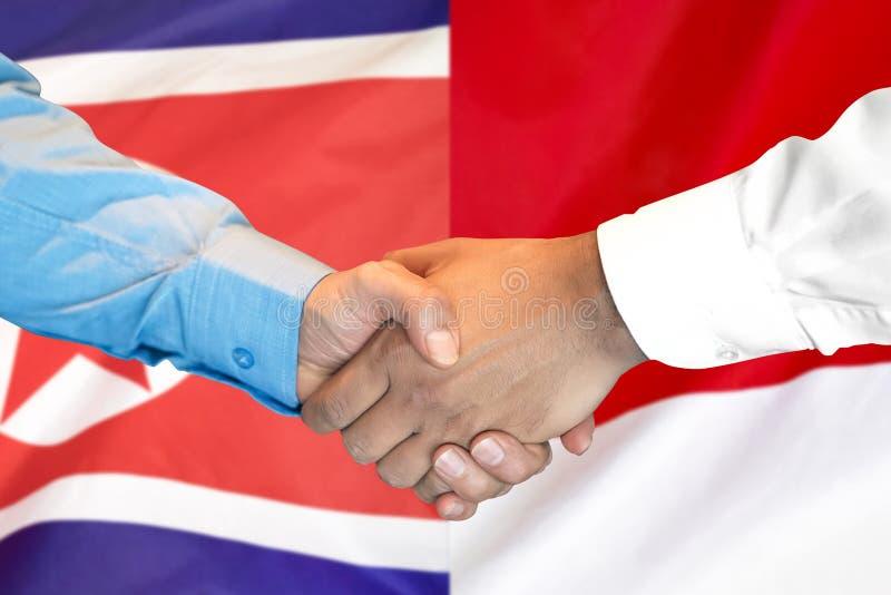 Aperto de mão fundo na bandeira da Coreia do Norte e do Mônaco fotografia de stock