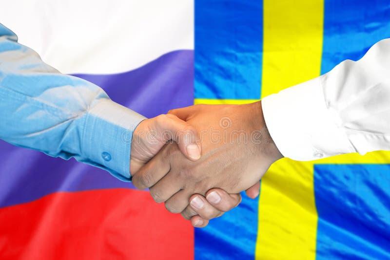 Aperto de mão fundo na bandeira da Suécia e da Rússia foto de stock royalty free