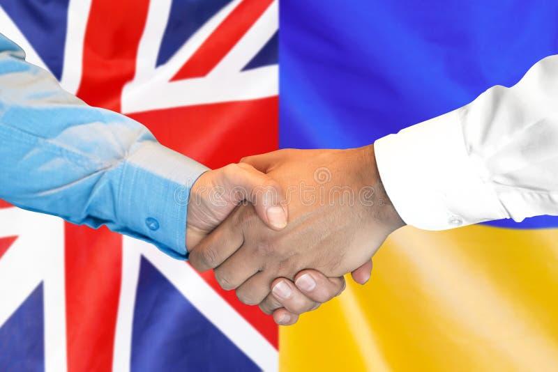 Aperto de mão no fundo da bandeira do Reino Unido e da Ucrânia imagens de stock royalty free