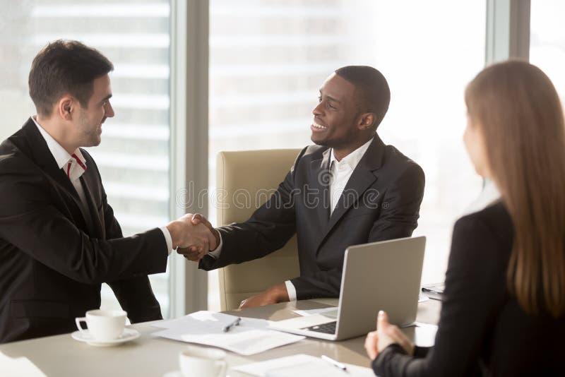 Aperto de mão preto e branco dos homens de negócios na reunião, fazendo o succe fotos de stock royalty free