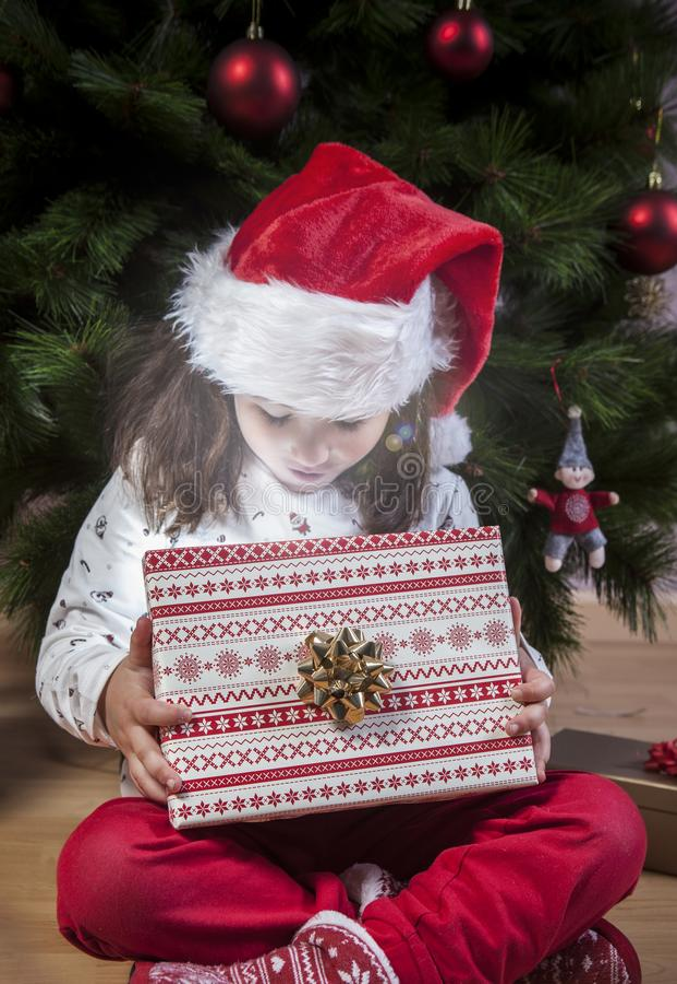 Apertura che della bambina presenta sotto l'albero di Natale immagini stock