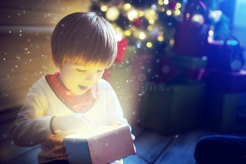 Apertura sorpresa del bambino e guardare dentro un regalo magico fotografie stock