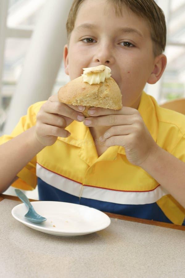 Apetito hambriento: Niño que come un mollete cocido al horno delicioso imagen de archivo