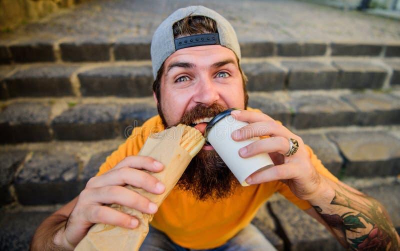 Apetito soltado Concepto de la comida de la calle El hombre barbudo come la salchicha sabrosa Nutrici?n urbana de la forma de vid foto de archivo libre de regalías