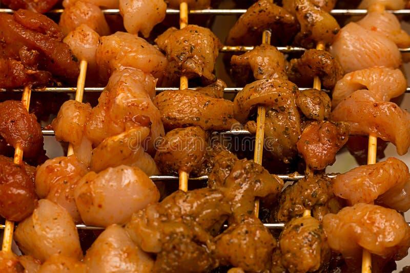 Apetitoso blando de la carne condimentado conservó en vinagre en especias picantes del curry en los pinchos de madera mucha base  fotografía de archivo