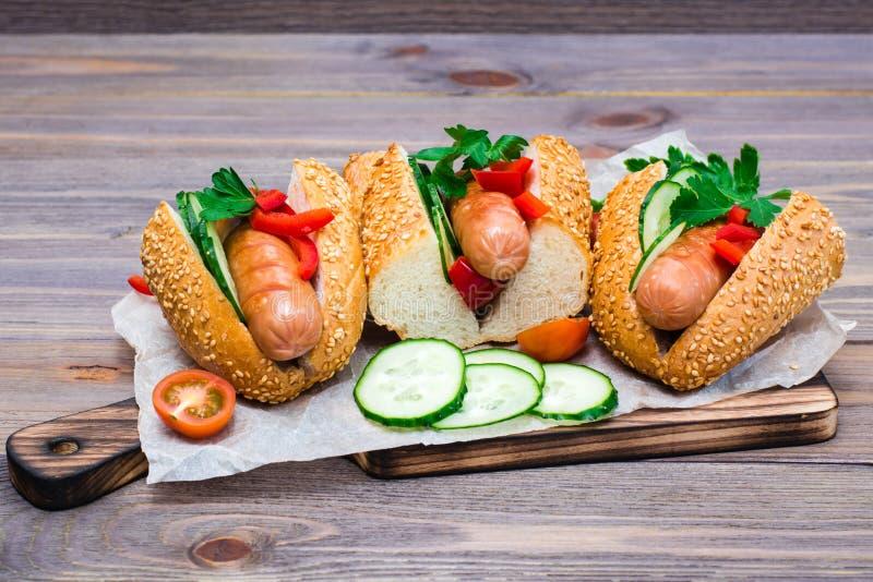 Apetyczni hot dog od sma?y? kie?bas, sezamowych babeczek i ?wie?ych warzyw na tn?cej desce, zdjęcie royalty free