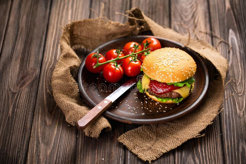 Apetyczny hamburger z pomidorami na stole obrazy stock