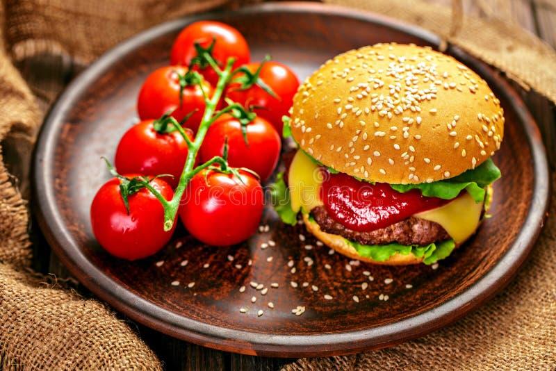 Apetyczny hamburger z pomidorami na stole zdjęcie royalty free