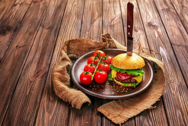 Apetyczny hamburger z pomidorami na stole obrazy royalty free