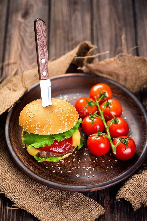 Apetyczny hamburger z pomidorami na stole obraz royalty free