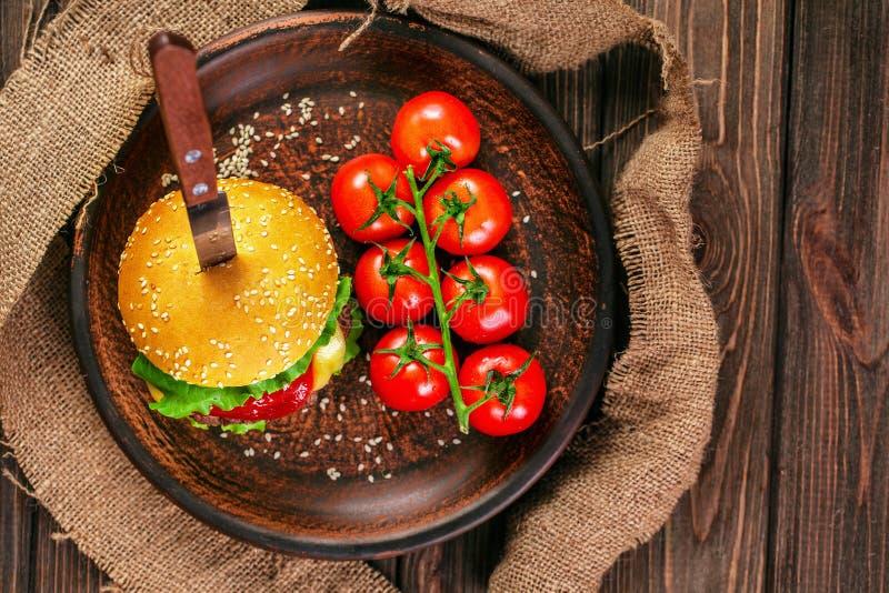 Apetyczny hamburger z pomidorami na stole zdjęcie stock