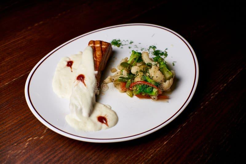Apetyczny naczynie na białym talerzu w rękach dziewczyna kelner, jedzenie fotografia stock