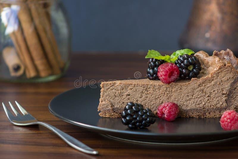Apetyczny plasterek czekoladowy cheesecake z jagodami obraz royalty free