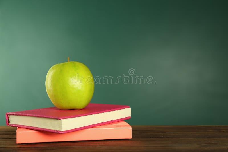 Apetyczny zielony jabłko i książki na drewnianym stole zdjęcia stock