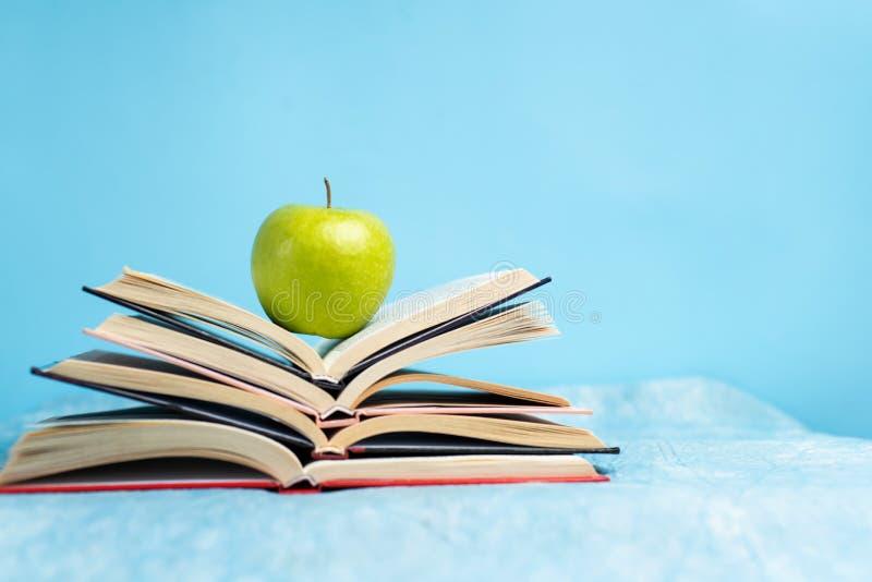 Apfel auf einem Haufen Bücher mit Kopierplatz stockfotografie