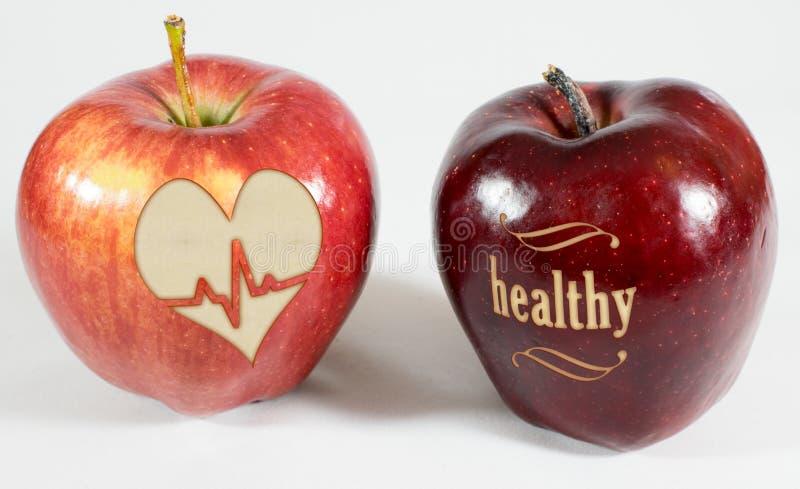 1 Apfel mit der Aufschrift gesund und ein Apfel mit einem Herzen lizenzfreie stockfotografie