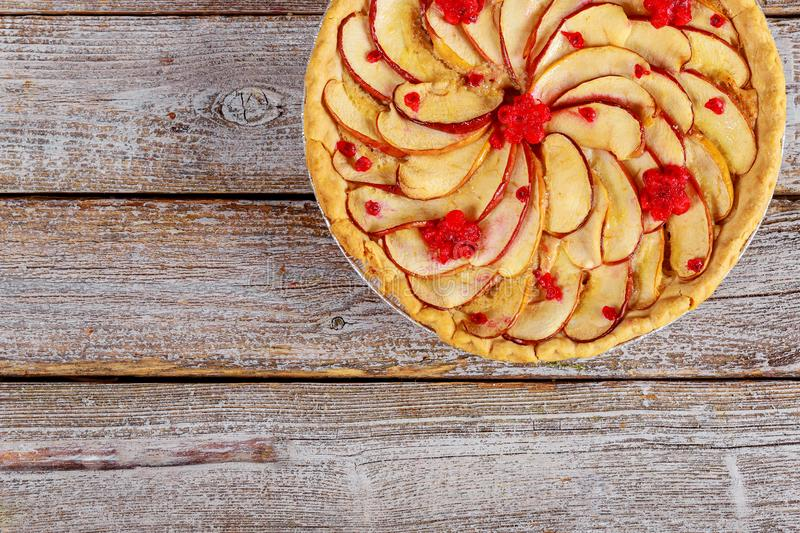 Apfelkuchen mit geschnittenen Äpfeln auf die Oberseite auf hölzernem Hintergrund lizenzfreie stockfotografie