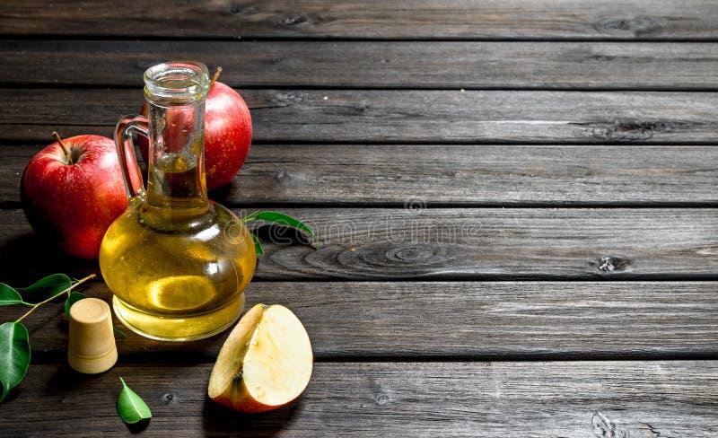 Apfelweinessig mit frischen Äpfeln lizenzfreie stockbilder