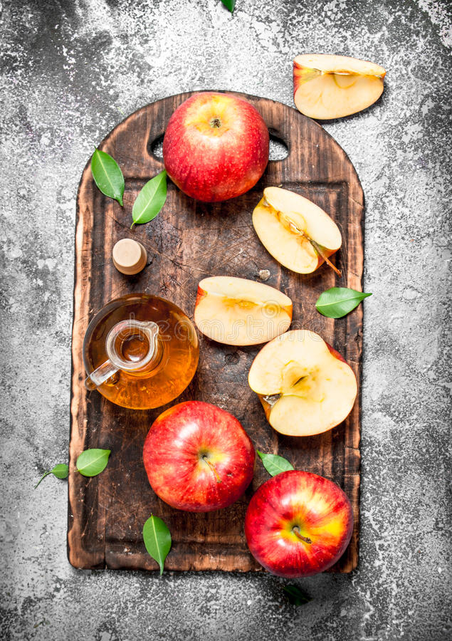 Apfelweinessig mit frischen Äpfeln auf Schneidebrett stockfotos