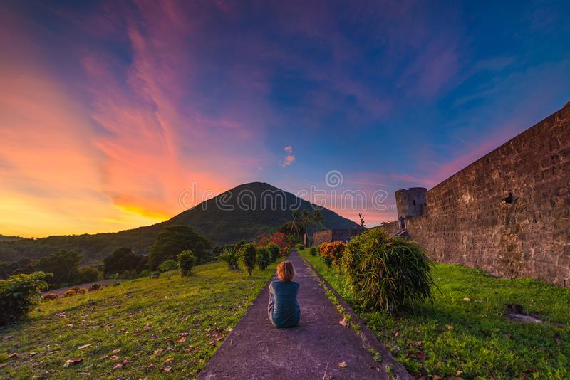 Api volcano at sunset, sitting woman looking at view from Banda Naira fort, Maluku Moluccas Indonesia, Top travel tourist royalty free stock photography