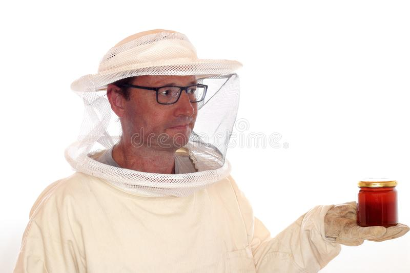 Apiarist is holding a honey glass. In hand stock images