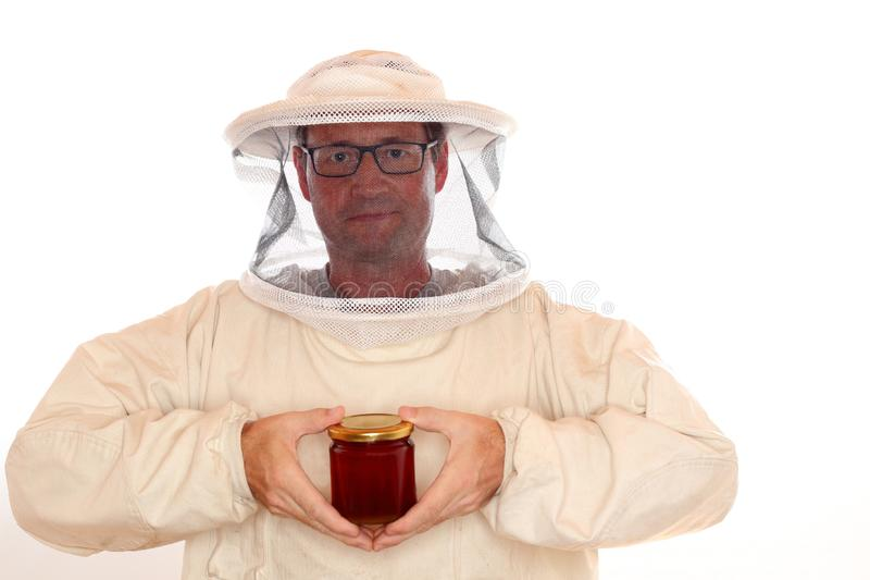 Apiarist with honey glass. In hand on white background royalty free stock images