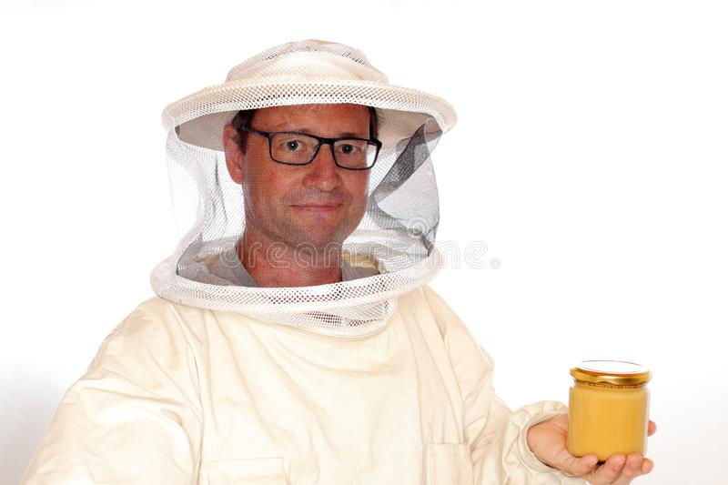 Apiarist and honey. Apiarist is holding a honey glass on white background royalty free stock photos