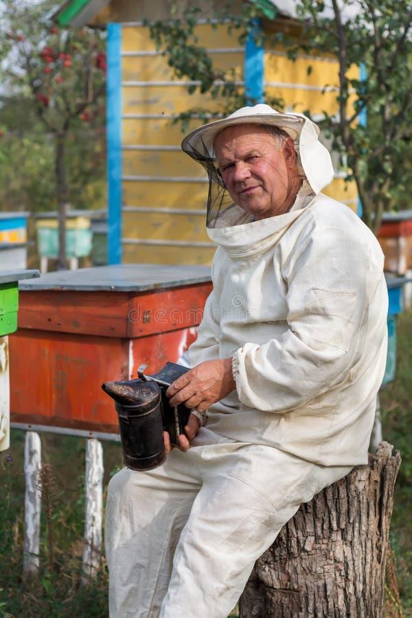 Apiculteur dans un rucher Apiculture images stock