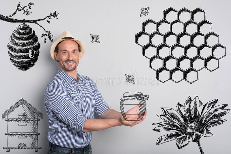Apiculteur heureux tenant un pot de miel et semblant heureux image libre de droits