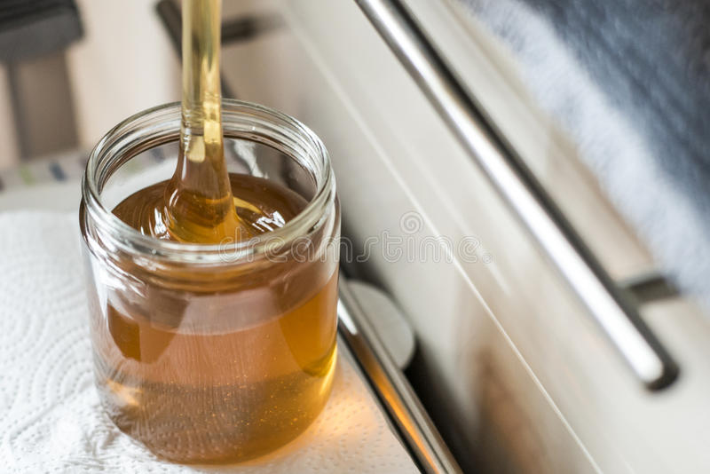 Apicultor que llena encima de la nueva miel de oro fresca en los tarros de cristal imagen de archivo libre de regalías