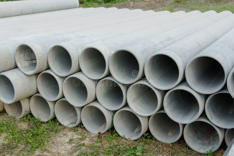 Apilado de concreto, tubos del cemento tubos concretos para la irrigación en el emplazamiento de la obra imagen de archivo